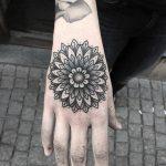 Simple black mandala on the hand