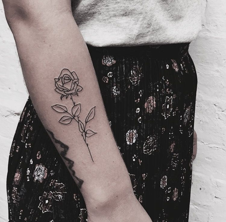 Simple black outline rose tattoo on the forearm