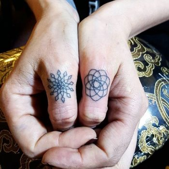 Small geoemtric tattoos on thumbs
