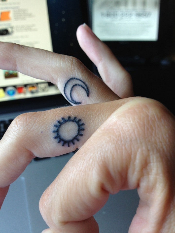 Small sun and moon tattoos on the fingers