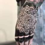 Solid black mandala tattoo on the hand