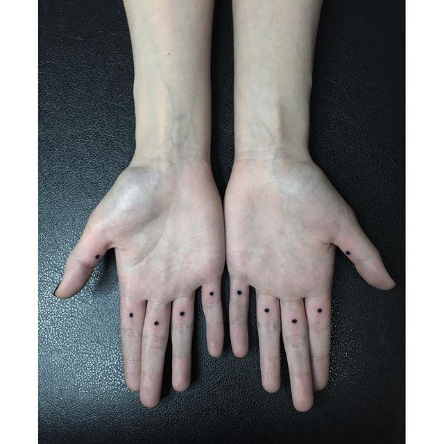 Tiny dot tattoos on fingers