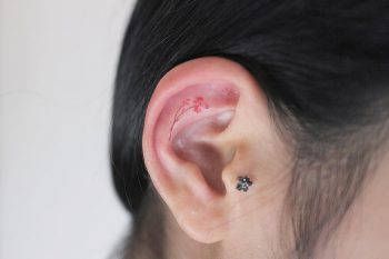 Tiny flower inner ear tattoo