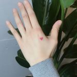 Tiny red heart tattoo on the hand