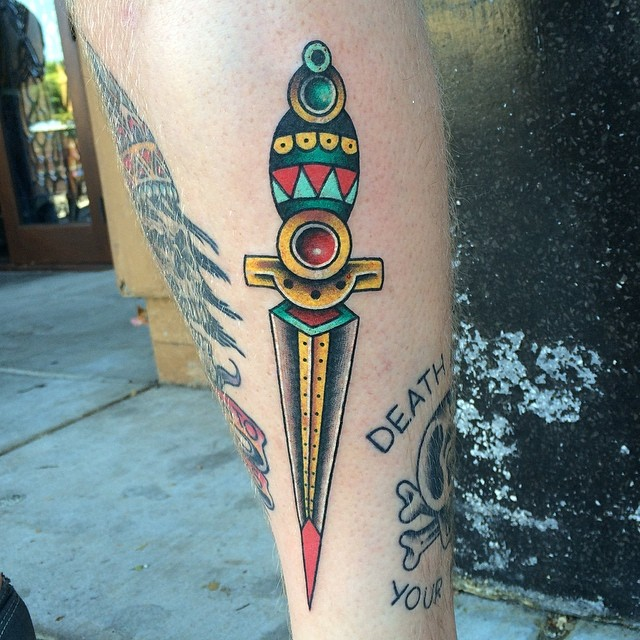 Traditional colorful dagger tattoo on the calf