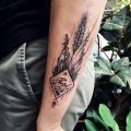 Wave in a rhombus and wild plants tattoo
