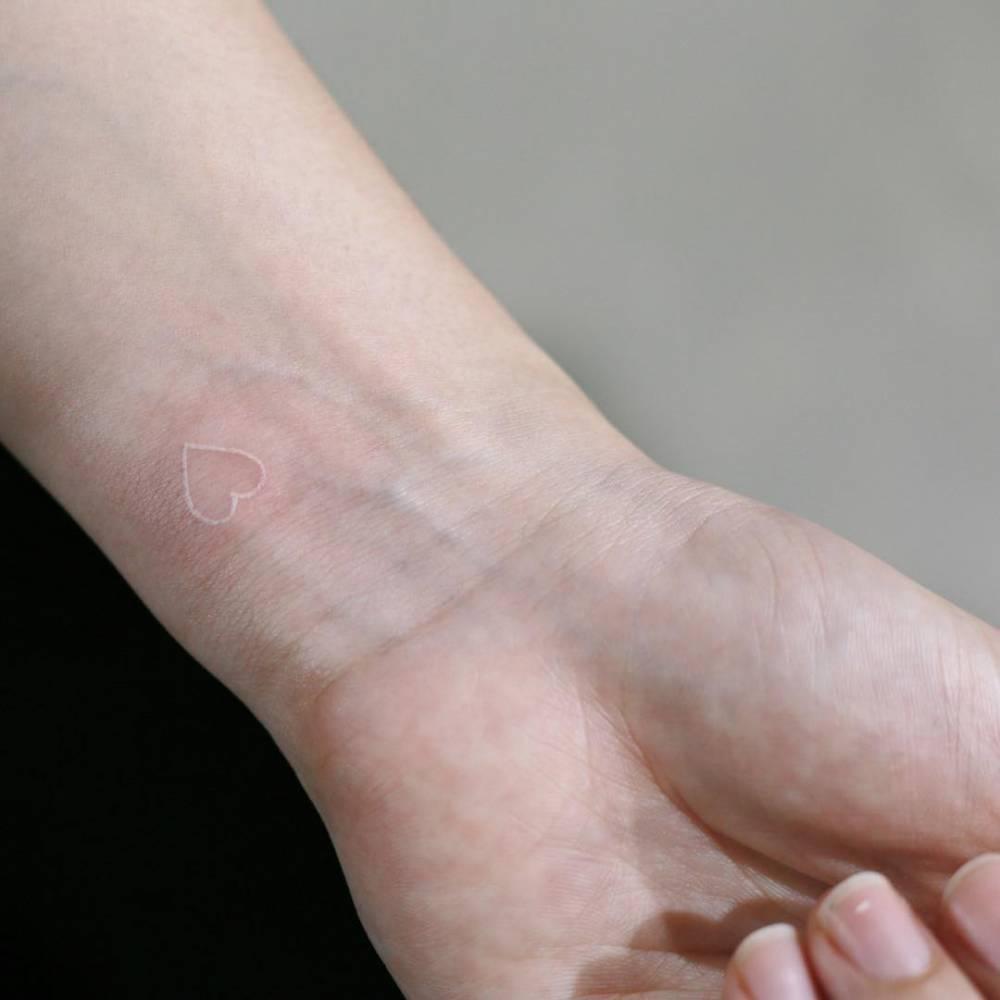 White hear tattoo on the wrist