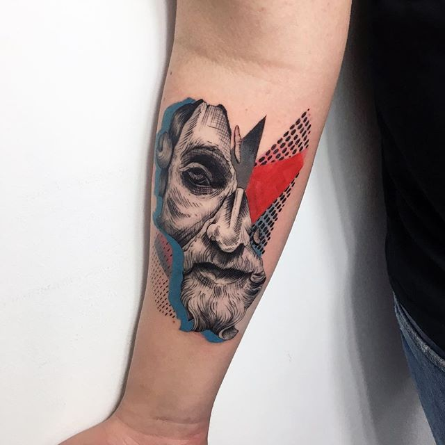 Abstract face tattoo on the forearm