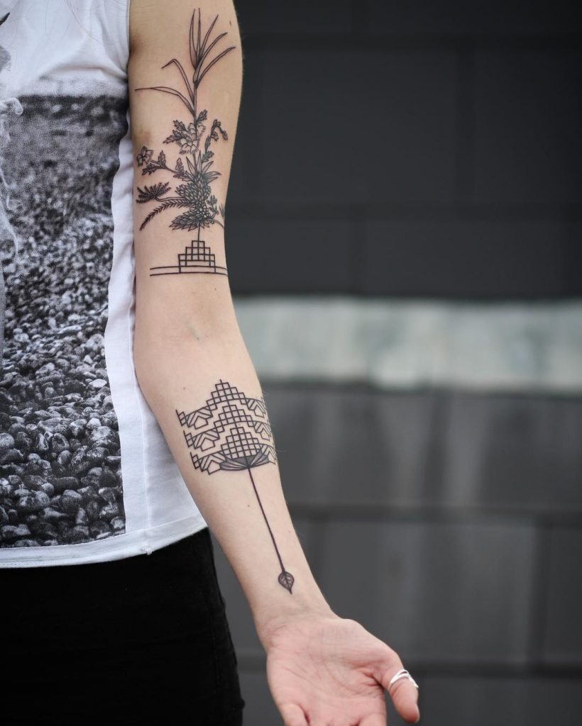 Beautiful geometric and flower tattoos on the arm