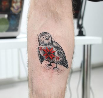 Bird with a red ornament tattoo