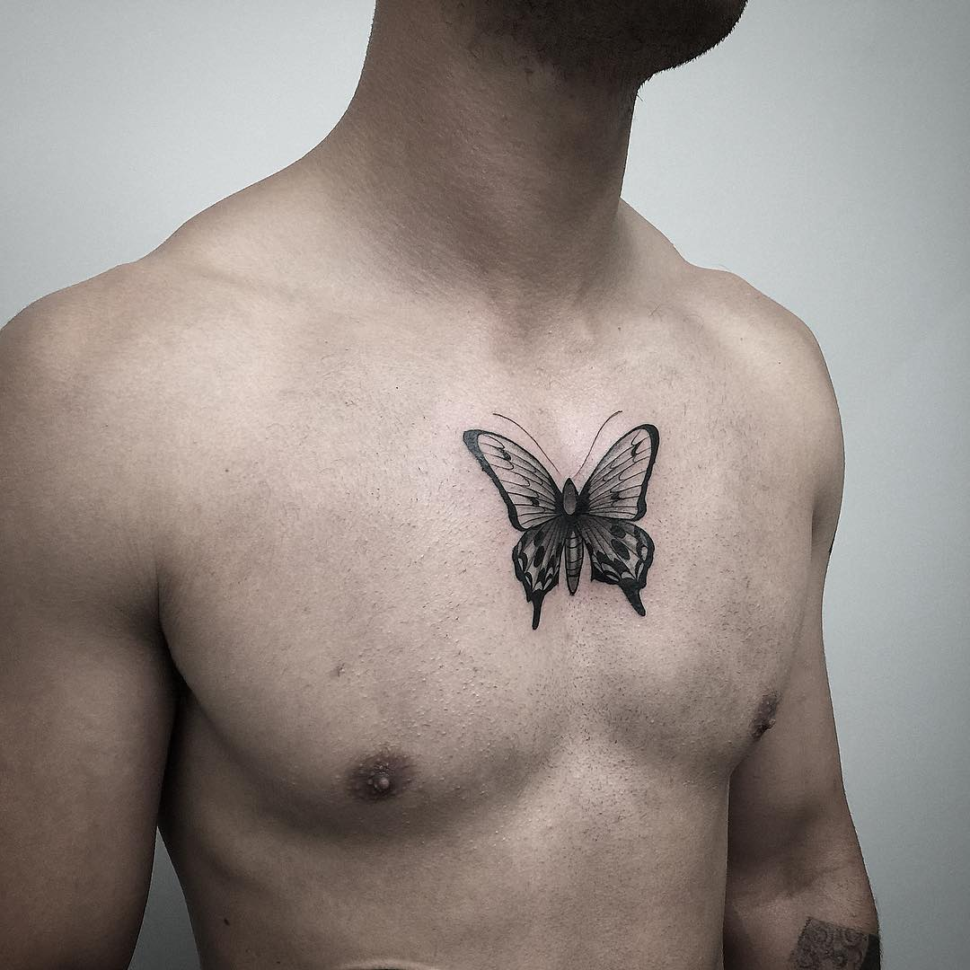 Black butterfly tattoo on chest