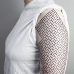 Black geometric pattern tattoo on the left arm