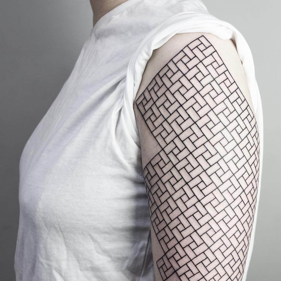Black geometric pattern tattoo on the left arm