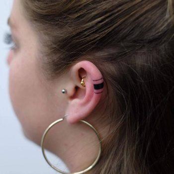 Black lines tattoo on the left ear