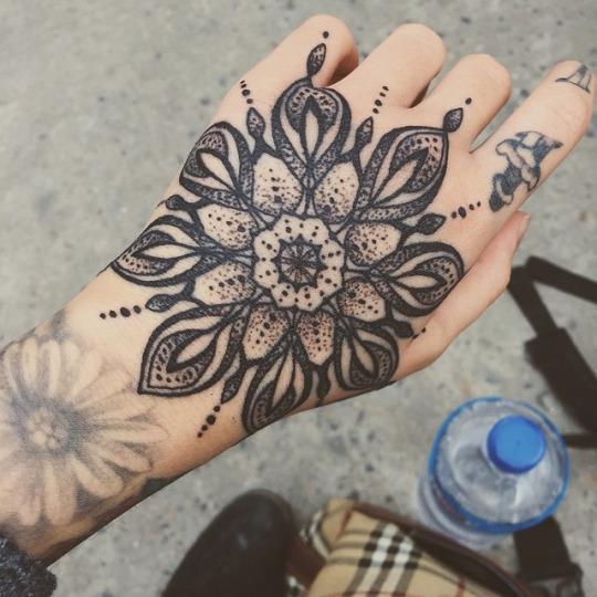 Black mandala tattoo on the left hand