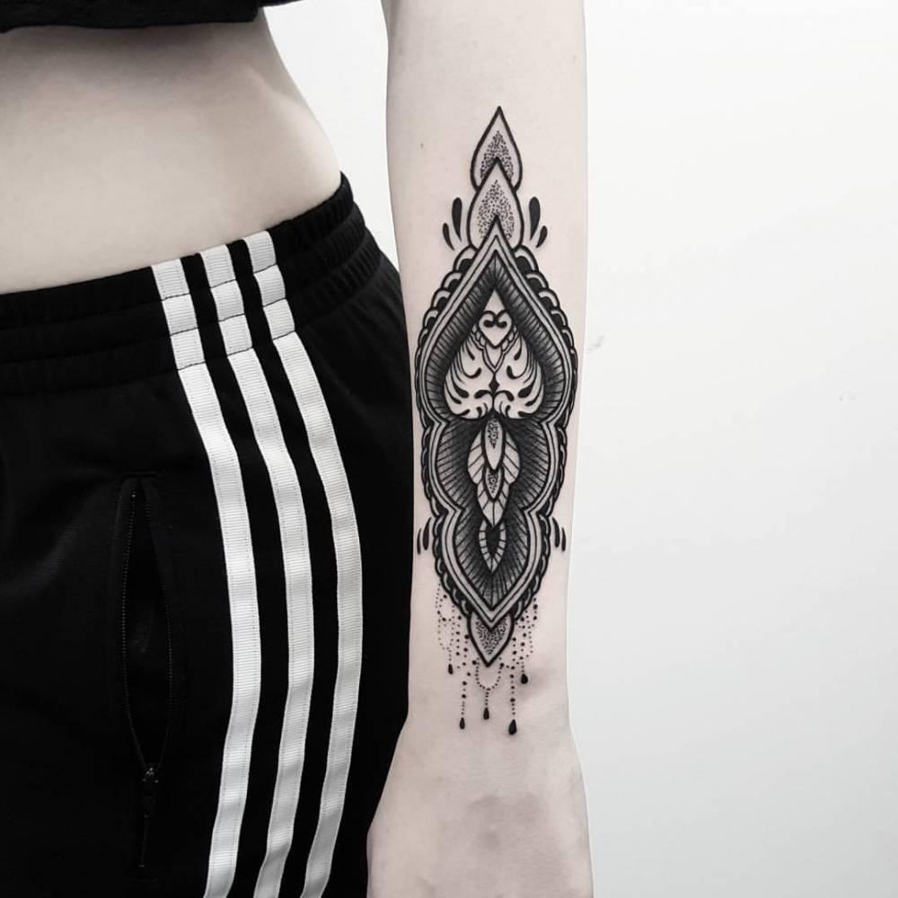 Black ornament tattoo on the left wrist