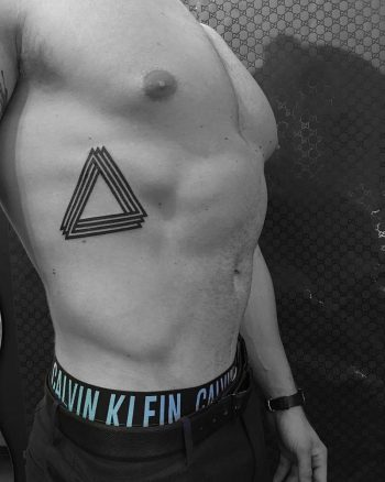 Black penrose triangle tattoo on the rib