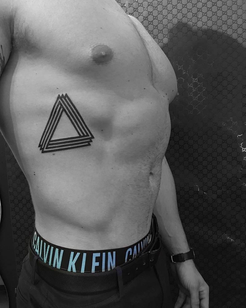 Black penrose triangle tattoo on the rib