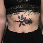 Black rose tattoo on the sternum