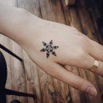 Black snowflake tattoo
