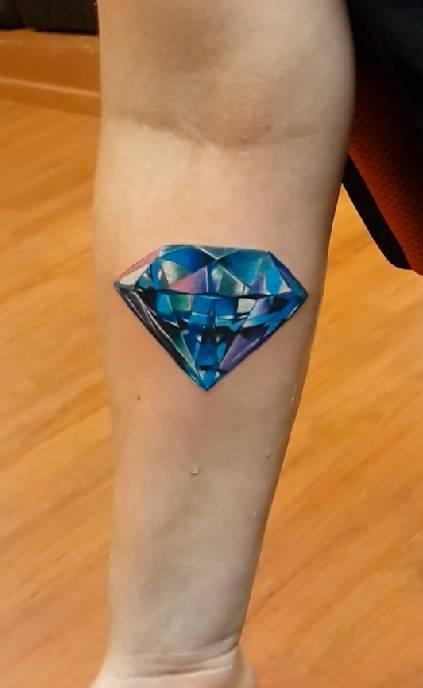 Blue diamond tattoo on the forearm