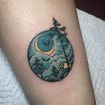 Circular mountain and forest landscape tattoo
