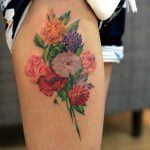 Colorful floral bouquet tattoo on the thigh