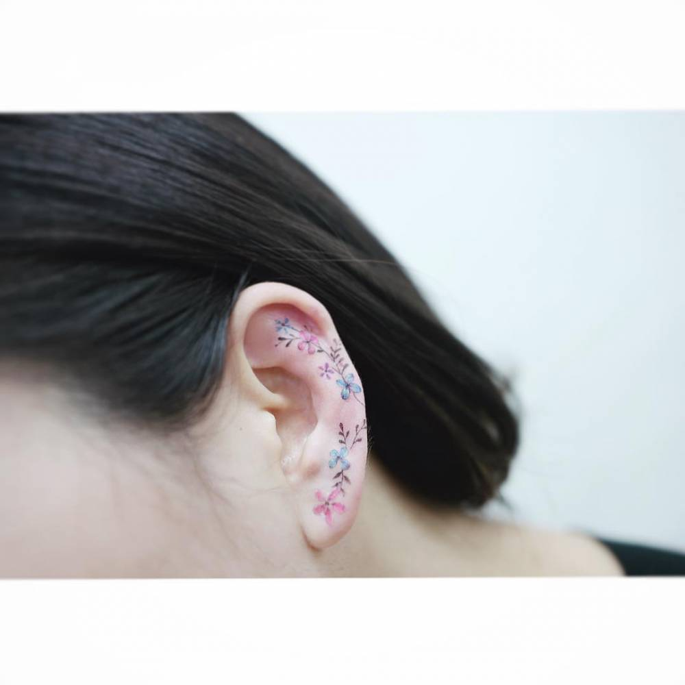 Colorful flower tattoo on the left ear