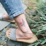 Colorful flowers tattoo on the left ankle
