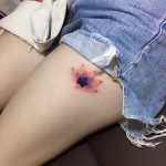 Colorful lotus flower tattoo on the thigh