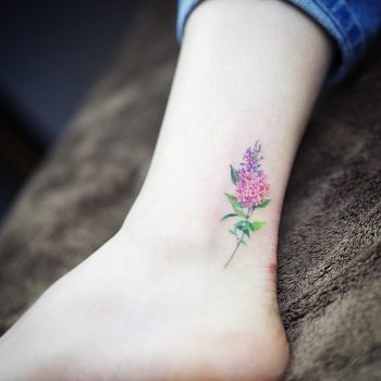 Delicate pink wildflower tattoo on the inner ankle