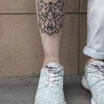 Geometric wolf head tattoo on the shin