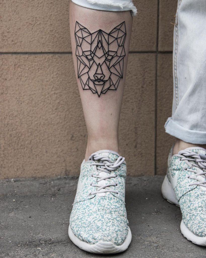 Geometric wolf head tattoo on the shin