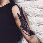 Magpie tattoo on the left arm