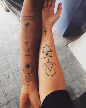 Matching black geometric ornaments tattoo