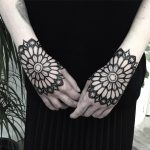 Matching black mandala tattoos on the hands