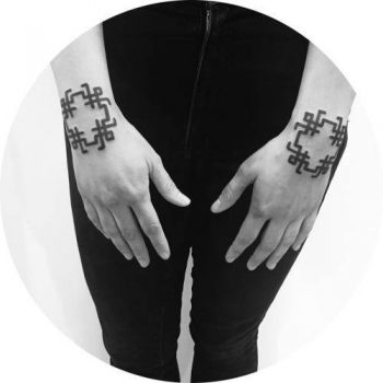 Matching black ornament tattoos on both hands