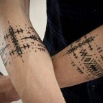 Matching black ornamental armband tattoos