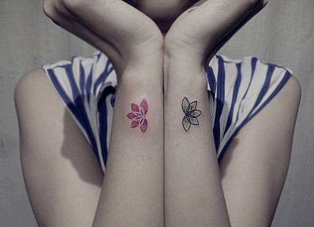 Matching lotus flower tattoos on wrists
