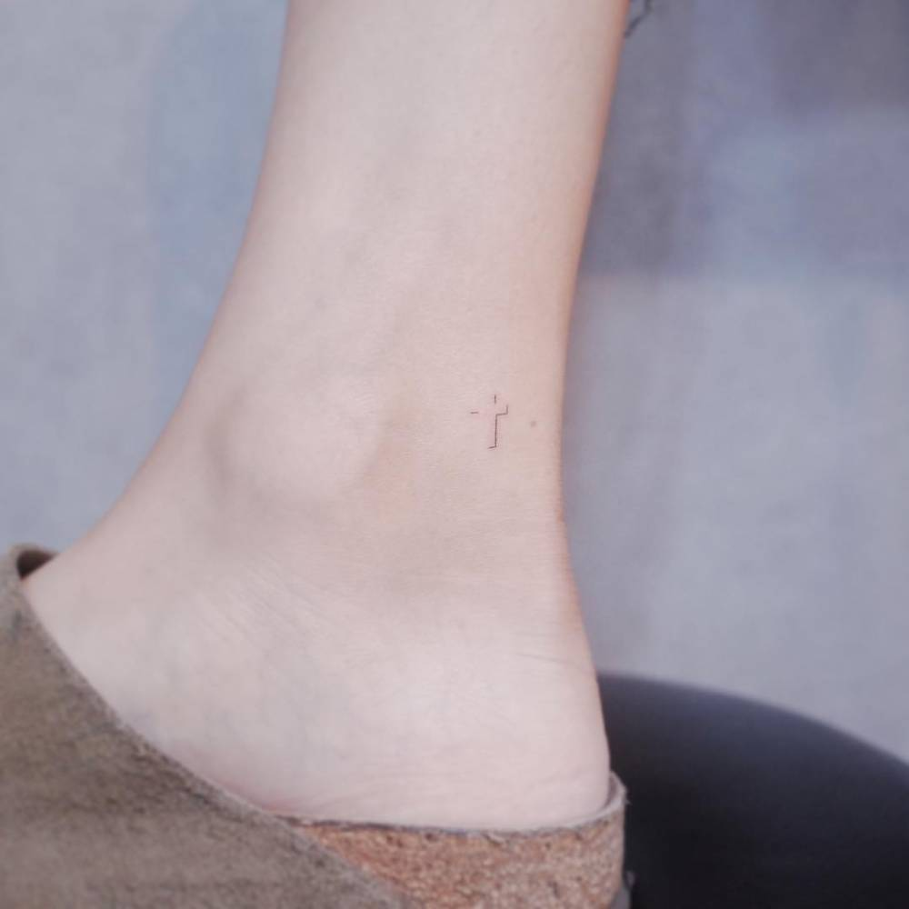 Micro cross tattoo on the inner ankle