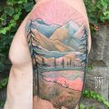 Mountainous landscape tattoo on the left arm