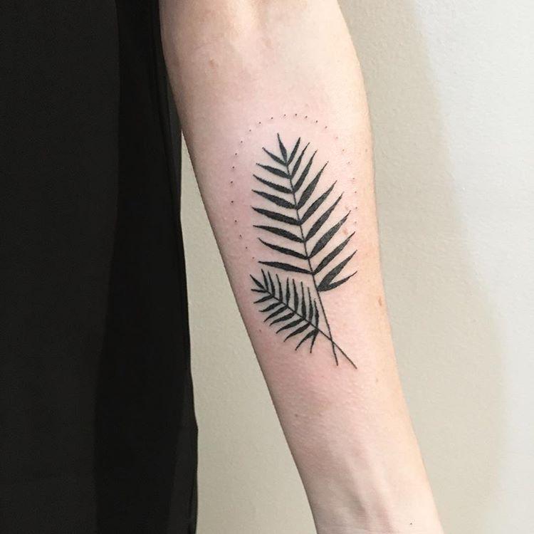 Palm leaf tattoo on the left inner arm