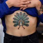 Peacock tattoo on the sternum
