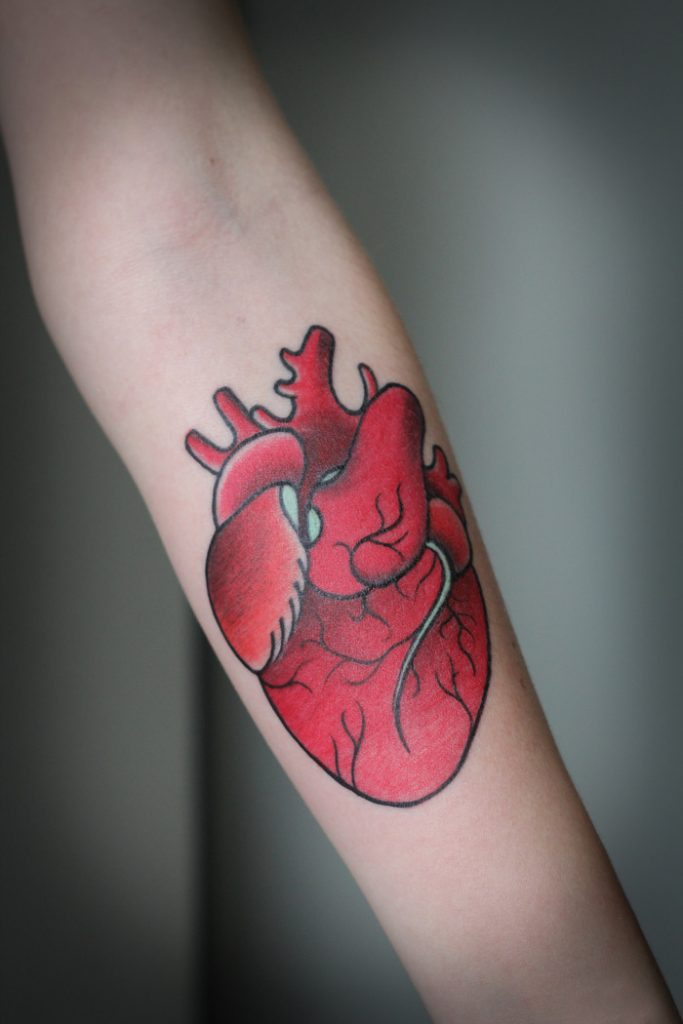 Red heart tattoo on the forearm