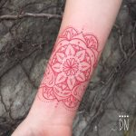 Red mandala tattoo on the inner wrist