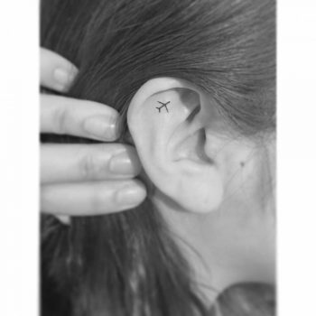 Small airplane tattoo on the ear