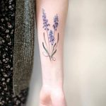 Subtle lavender tattoo on the left inner forearm
