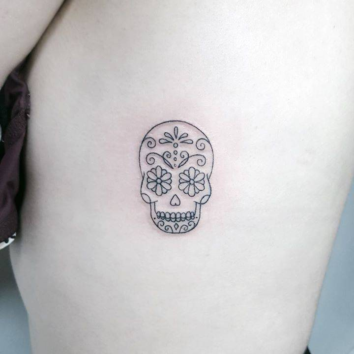 Sugar skull tattoo on the rib