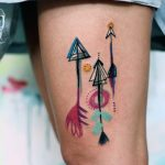 Three watercolor arrow tattoos on the left thigh