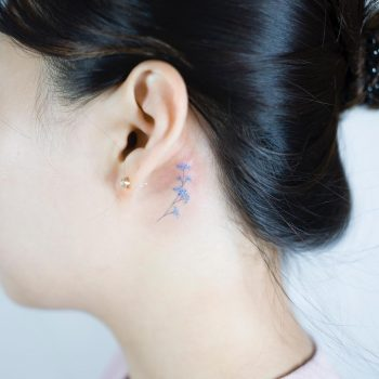 Tiny blue flower behind the ear tattoo